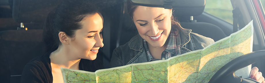 Mother and daughter looking at a map in a car
